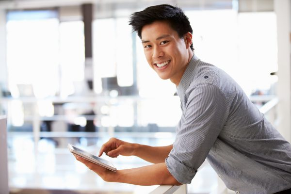 Portrait of man in office using tablet smiling to camera