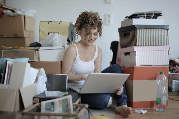 Lady Smiling On Laptop Surrounding By Boxes